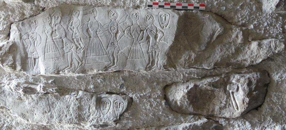 Personnages datés du XIVe siècle, oiseaux, têtes stylisées et outil (?), gravés sur des blocs d'une archère de la tour nord-est.