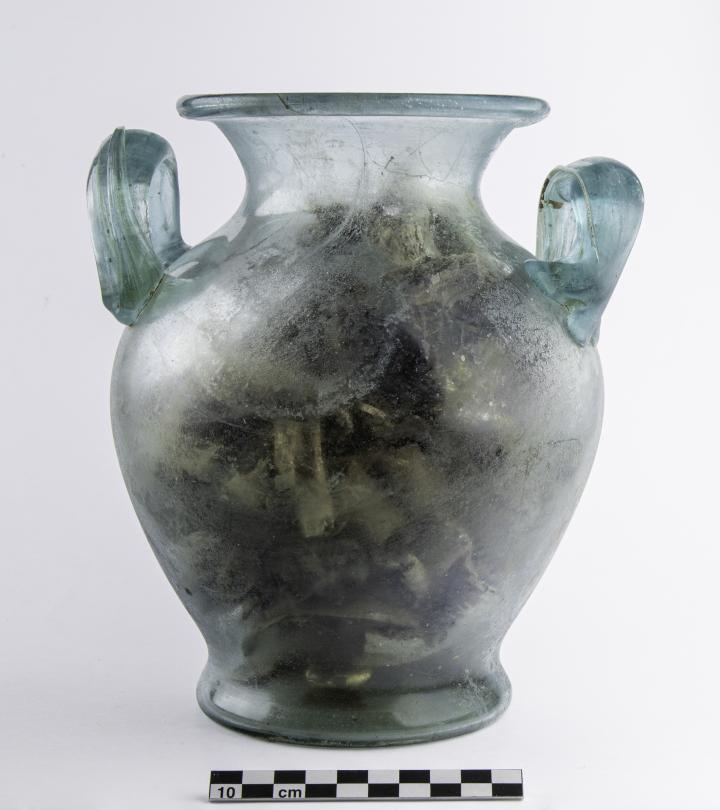 Vase ossuaire en verre contenant des fragments osseux brûlés et, dans le fond, une bague en or.