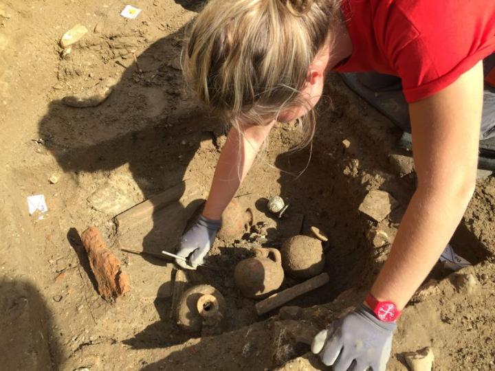 Fouilles autour de cruches et vase à parfum en verre trouvés sur des ossements brûlés d'un défunt