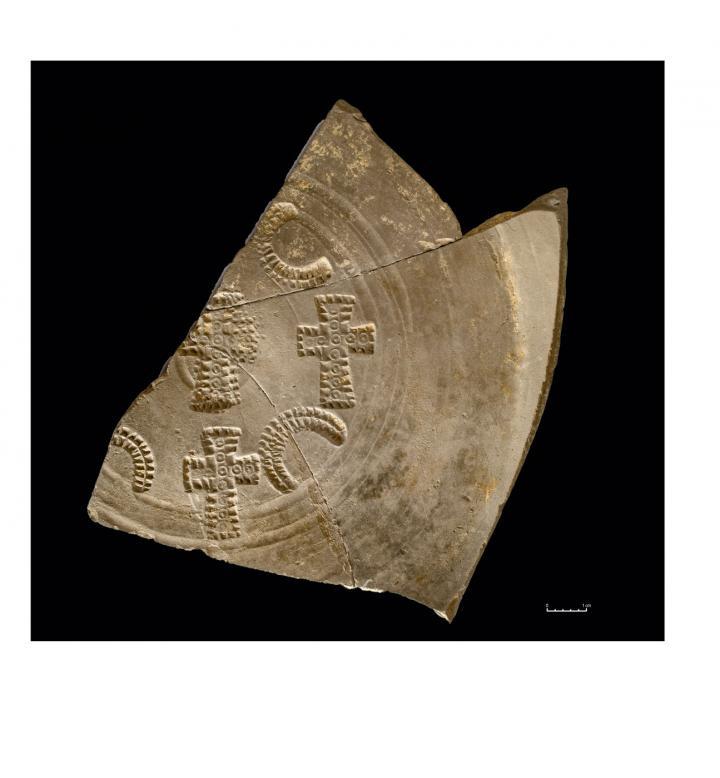 Un fragment de plat en céramique dérivée de sigillée paléochrétienne ornée de poinçons cruciformes, témoignant jusque dans le décor des objets du quotidien de l'influence du christianisme.