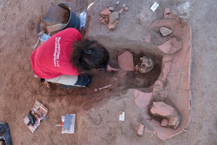 Une archéologue de l'Inrap est en train de fouiller une sépulture médiévale en pleine terre ayant recoupée une sépulture en amphore africaine antérieure.
