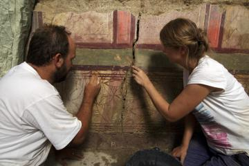 Marie-Pierre Rothé (responsable de l'opération archéologique, MDAA) et Julien Boislève (responsable de l'études des enduits peints, Inrap), dégagement en cours de la paroi peinte.