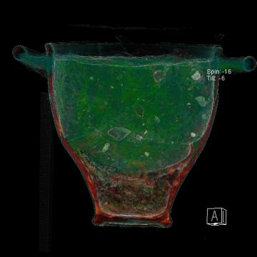 Analyse tomodensitométrique d'un skypos (vase) et de son contenu découverts dans la chambre funéraire. La restitution en volume permet de faire apparaître une coupelle au sein de celui-ci. Les couleurs sont artificielles et ont été définies en fonction de l'absorption des rayons X par les types de matériaux. Analyse réalisée en post-fouille par la société BCRX.