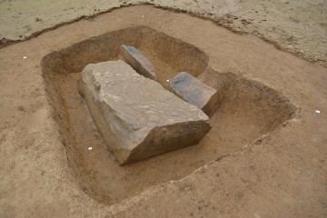 Vue des trois blocs  en cours de fouille, dont la stèle face décorée contre le sol.