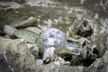 Vase à parfum en verre en forme d'amphore, déposée sur les restes osseux brûlés au sein d'un vase ossuaire en pierre.