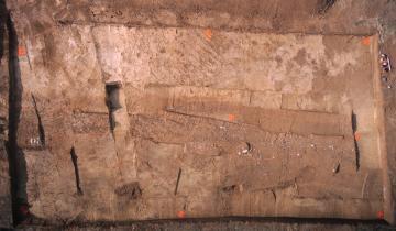 Vue aérienne de la voie antique et de ses fossés bordiers après terrassement dans le secteur oriental de la fouille.  Castelle, Lattes (Hérault), 2013. © Drone Concept, Inrap