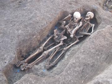 Vue de sépultures rupestres d'époque médiévale superposées et contenant les squelettes de trois femmes d'âge mûr à âgé.