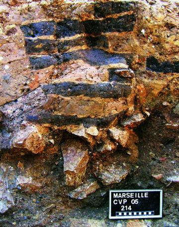 Mur en adobe (briques de terre crue) mis au jour au collège Vieux-Port à Marseille, VIe s. avant notre ère, 2005.  Les briques sont posées sur un solin de pierre et sont séparées par des joints argileux plus clairs. La fouille a permis d'étudier les premi