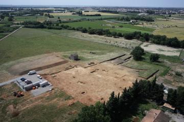 Vue aérienne du décapage sur le site néolithique final de Cadoules, dans la plaine de Mauguio. L'assombrissement des sédiments, visible au centre gauche de la photo, marque un ancien chenal de la rivière qui apparaît au second plan (rangée d'arbres). Cadoules, Mudaison (Hérault), 2013. © Archéodrone/Inrap.