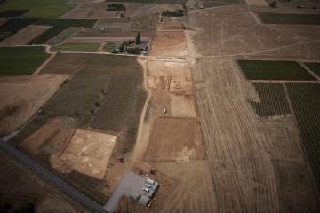 Vue aérienne depuis le nord-est du décapage du site du Péras. On distingue les trois secteurs de fouille : Péras 2, au premier plan à gauche, et les deux autres, qui constituent  Péras 1, en haut de l'image de part et d'autre d'un chemin orienté nord-ouest/sud-est. Le Péras, Mauguio (Hérault), 2013. © Archéodrone, Inrap