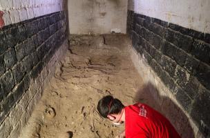 Fouille d'une fosse commune (salle 6) recoupée par les murs de la cave