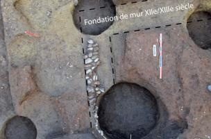 Diverses fosses médiévales et un mur partiellement récupéré recoupant des remblais antiques