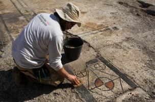 Nettoyage d'un seuil à motif géométrique d'une mosaïque antique mise au jour à Uzès (Gard), 2017.