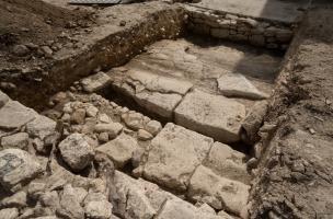 Une chaussée dallée antique équipée d'un caniveau borde le bâtiment à la mosaïque antique découverte à Uzès (Gard), 2017.