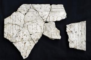 Plaque en marbre mise au jour lors des fouilles effectuées au Faubourg d'Arroux à Autun en 2010, datée des environs du IIe s. de notre ère et réemployée dans un sol de trottoir du IIIe s.  Elle accueille une dédicace à un chevalier romain, tribun militai