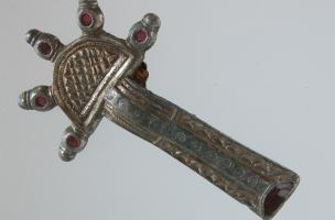 Fibule ansée et asymétrique en argent, découverte en 2003 dans la sépulture aristocratique n°12 de Saint Dizier (Haute-Marne)qui estdatée du VIe s. de notre ère.  Elleest composée d'une tête de forme semi-circulaire portant un décor quadrillé, prolon