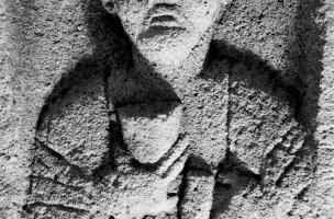 Stèle funéraire gallo-romaine en arkose (hauteur 74 cm, largeur 43 cm), nécropole de Pont-L'Évêque, Autun (Saône-et-Loire), 2004.  La tête de ce personnage en buste a été sculptée avec soin, lui donnant une expression sévère. Sa main droite tient un grand