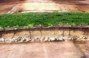 Coupe transversale de la voie antique reliant Vannes à Angers, Allaire (Morbihan), 2005.  Cette coupe indique l'existence d'un bombement épais de plus d'un mètre, constitué de recharges successives établies sur la fondation empierrée, dont la largeur atte