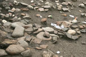 Vue rapprochée d'un niveau de sol du Néolithique moyen chasséen (IVe millénaire avant notre ère) sur le site des Queyriaux à Cournon-d'Auvergne (Puy-de-Dôme), 2011.  Des galets et le mobilier - ici de gros fragments de céramique - posés à plat jonchent le