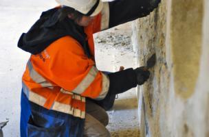 Enlèvement des enduits récents sur un des murs du couvent des Jacobins à Rennes (Ille-et-Vilaine), 2012.  Cette opération permet de révéler les anciennes maçonneries de l'édifice dans le cadre de l'étude du bâti.