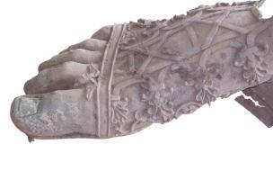 Pied droit d'une statue colossale en bronze découvert sur le sol d'une cour attenante à une domus, début du IIes. de notre ère,Clermont-Ferrand (Puy-de-Dôme), 2007.Long de plus de 60 cm, le pied est chaussé d'une botte lacée richement décorée de rinceau