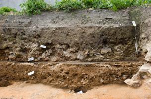 Stratigraphie d'une maison avec un niveau de sol en terrazzo, Metz (Moselle), 2012.  Les fouilles menées rue Mazarin ont délivré les vestiges inattendus d'un faubourg médiéval dont la destruction serait liée au siège de Metz par les troupes de Charles Qui