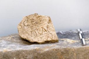 Fragment de plaque funéraire avec inscription, Metz (Moselle), 2012.  La diversité des modes d'inhumation et du mobilier funéraire atteste une utilisation du cimetière durant plusieurs siècles au Moyen Âge.