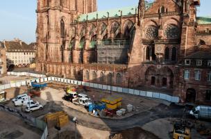 au premier plan le terrassement d'une tranchée de 5 m de profondeur ; à l'arrière plan, au sud de la cathédrale, la zone de fouille.