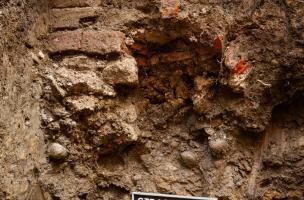 Vue d'un mur observé en suivi de réseau dans une tranchée creusée place du Château à Strasbourg (Bas-Rhin), 2012.  La structure est un angle de bâtiment dont la base de la maçonnerie est constituée de tuiles romaines plates à rebord (tegula) superposées l