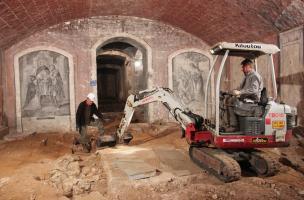 Décapage mécanisé dans la crypte de la basilique Notre-Dame de Boulogne-sur-Mer (Pas-de-Calais), 2012. Dans la nef de la crypte, la fouille a mis en évidence des niveaux archéologiques antérieurs à la construction des premiers remparts connus du camp de l