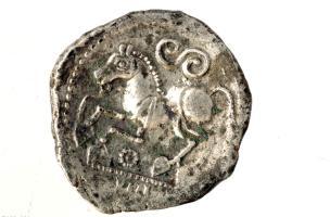 """Monnaie d'argent figurant un cheval au galop et un """"S"""" celtique qui représente un serpent, Iers. avant notre ère, Bassing (Moselle), 2010.Cette iconographie classique du monde gaulois est fortement représentée dans le dépôt monétaire de Bassing."""