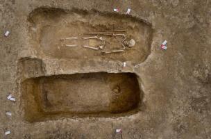 Deux sépultures juxtaposées, IVes. avant notre ère, Buchères (Aube), 2013.La tombe du bas de la photo n'a pas été fouillée, on voit apparaitre les ossements du crâne sur la droite et la trace noire délimite le contour du coffre qui contenait le défu