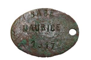 """Avers de la plaque d'identité du soldat Babé portant l'inscription """"Babé Maurice 1917"""".Cet élément a permis l'identification précise de ce combattant """"tué à l'ennemi"""" le 30 août 1918 dont le corps n'avait jamais été retrouvé. Sa découverte fortuite a été"""