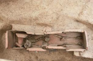 """Vue de l'intérieur du coffrage en tuiles de la tombe à libations, Ier-IIIes. de notre ère, Portbail (Manche), 2012.Une jeune femme y est inhumée avec deux pièces de monnaie en bronze, expression du rite de """"l'obole à Charron"""". Sur la gauche, le coussin c"""
