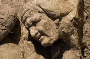 Vue de détail du visage de la vieille servante chuchotant la cachette de Vénus, IIe s. de notre ère, bas-reliefs de la façade monumentale du sanctuaire gallo-romain de Pont-Sainte-Maxence (Oise), 2014.