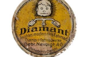 """Emblème publicitaire de vélo de la marque """"Diamant"""". Ce vélo est fabriqué dans l'usine de Chemnitz (Allemagne) par les frères Nevoigt depuis 1885. Découvert en surface d'une fosse allemande datant de la Grande Guerre à Saint-Etienne-sur-Suippe (Marne), 20"""