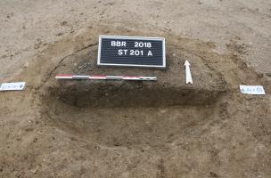 Dépôt des restes osseux fragmentés mêlés aux résidus du bûcher dans la sépulture 201, à Bitry