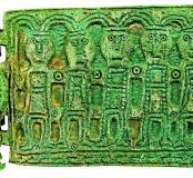 Plaque-boucle du type Niederwangen, bronze coulé, VIIe-VIIIe s., Marchaux (Doubs), 2001-2004.  L'objet présente un décor de six personnages, peut être la moitié du collège apostolique. Le Christ serait représenté par le visage barbu sur l'ardillon, à gauc
