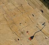 Vue aérienne de bâtiments gallo-romains à Brielles (Ille-et-Vilaine), 2011.Des tâches sombres dessinent au sol le plan carré d'une vaste construction d'environ 500 m2. Il s'agit de fosses autrefois creusées pour accueillir les poteaux, aujourd'hui disparu